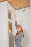Smiling young girl measuring wall with tape measure Royalty Free Stock Photos