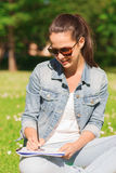 Smiling young girl with notebook writing in park Royalty Free Stock Photo