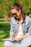 Smiling young girl with notebook writing in park Stock Images