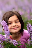 Smiling Young Girl in Patch of Wild Flowers. A cute smiling young girl with dark hair in a patch of purple wild flowers. Shallow depth of field Royalty Free Stock Image