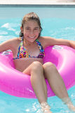 Smiling young girl in a pink buoy at the pool Stock Photo