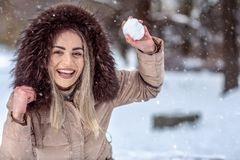 Smiling girl playing snowball fight on the winter snow day. Smiling young girl playing snowball fight on the winter snow day royalty free stock photo
