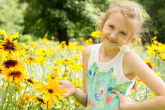 Smiling young girl playing in yellow flowers Stock Photo