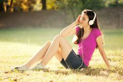 Happy Girl Listening to Headphones on a Wonderful Autumn Day royalty free stock photo