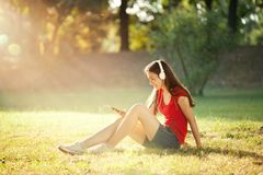 Happy Girl Listening to Headphones on a Wonderful Autumn Day royalty free stock image