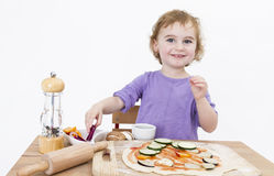 Smiling young girl preparing fresh pizza Stock Photography