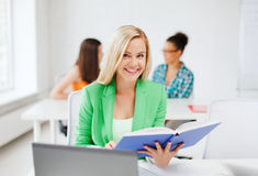 Smiling young girl reading book at school Stock Images