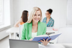 Smiling young girl reading book at school Stock Photos