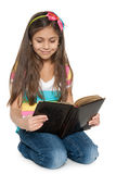 Smiling young girl reads an old book. A smiling young girl is reading an old book Stock Photos
