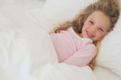 Smiling young girl resting in bed Stock Photo
