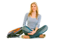 Smiling young girl with schoolbag sitting on floor Royalty Free Stock Photography