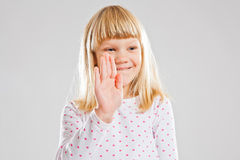 Smiling young girl showing hand signal Stock Image