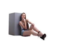 Smiling young girl sits leaning against cube Royalty Free Stock Photography