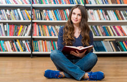 Smiling young girl sitting on the floor in the library with cros Royalty Free Stock Image