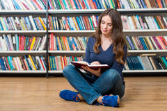 Smiling young girl  sitting on the floor in the library reading Stock Photos