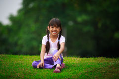Smiling young girl sitting on green grass Stock Image