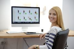 Smiling young girl sitting at her workplace Stock Images