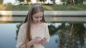 Smiling young girl sitting on the promenade of the river. stock video footage
