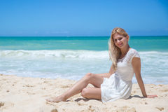 Smiling young girl sitting on the sandy beach Stock Photos