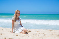 Smiling young girl sitting on the sandy beach Stock Photo