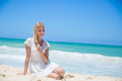 Smiling young girl sitting on the sandy beach Royalty Free Stock Photos