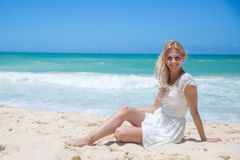 Smiling young girl sitting on the sandy beach Royalty Free Stock Images