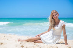 Smiling young girl sitting on the sandy beach Royalty Free Stock Image