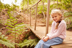 Smiling young girl sitting on a wooden bridge in a forest Royalty Free Stock Image