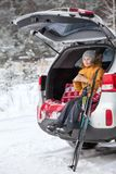 Smiling young girl skier sitting inbuilt compartment for luggage of car and drinking hot tea from cup. Winter wood. S Royalty Free Stock Images