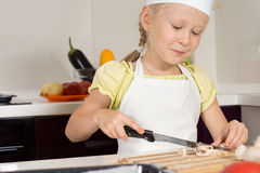 Smiling young girl slicing mushrooms for dinner Royalty Free Stock Photos