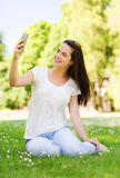 Smiling young girl with smartphone sitting in park Stock Image