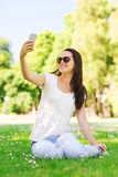 Smiling young girl with smartphone sitting in park Royalty Free Stock Photos