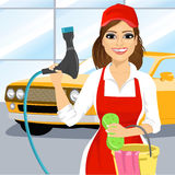 Smiling young girl with a soapy sponge and hose to wash a car Royalty Free Stock Photos