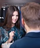 Smiling young girl speaks to shop assistant Stock Photos