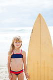 Smiling young girl standing next to surfboard stock photography