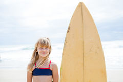 Smiling young girl standing next to surfboard Royalty Free Stock Photography