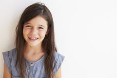 Smiling Young Girl Standing Outdoors Against White Wall Stock Image