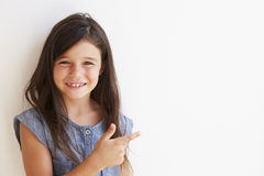 Smiling Young Girl Standing Outdoors Against White Wall Stock Photo
