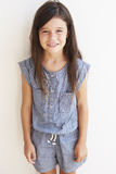Smiling Young Girl Standing Outdoors Against White Wall Royalty Free Stock Images