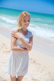 Smiling young girl standing on the sandy beach Stock Image