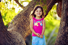 Smiling young girl standing on tree branches Royalty Free Stock Image