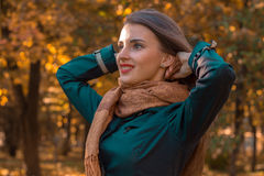 Smiling young girl stands sideways in the Park and keeps hands hair closeup Royalty Free Stock Images