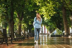 Smiling young girl student with backpack carrying books. Walking at the park Stock Image