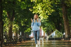 Smiling young girl student with backpack. Holding mobile phone, walking at the park Royalty Free Stock Image