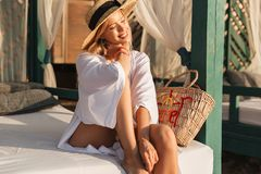 Smiling young girl in summer hat and swimwear resting. At the beach Stock Image
