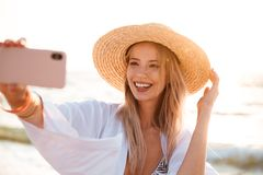 Smiling young girl in summer hat. And swimwear spending time at the beach, taking a selfie with outsretched hand Royalty Free Stock Photography