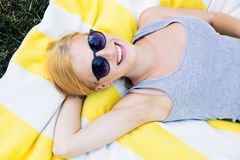 Smiling young girl in sunglasses lying on mat Stock Photo