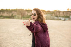 Smiling young girl in sunglasses walking on a beach Stock Photos