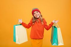 Smiling Young girl in sweater and hat holding packages. While looking at the camera over orange background stock photography
