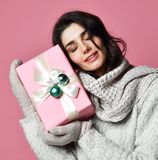 Smiling Young girl in sweater and mittens holding gift box royalty free stock photos